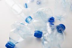 Chiuda su delle bottiglie di plastica utilizzate vuote sulla tavola Immagini Stock