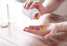 Chiuda su delle capsule di versamento dell'olio di pesce dell'uomo per passare Immagine Stock Libera da Diritti