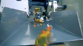 Chiuda su delle caramelle che ottengono concluse e che cadono lungo la condotta stock footage