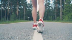 Chiuda su delle caviglie femminili che iniziano correre al rallentatore Atleta femminile che pareggia video d archivio