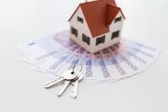 Chiuda su delle chiavi domestiche del modello, dei soldi e della casa Immagine Stock