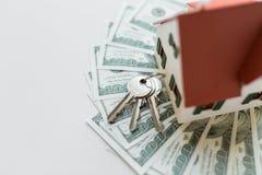 Chiuda su delle chiavi domestiche del modello, dei soldi e della casa Fotografie Stock