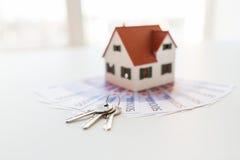 Chiuda su delle chiavi domestiche del modello, dei soldi e della casa Fotografia Stock