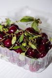 Chiuda su delle ciliege rosse in recipienti di plastica Immagini Stock Libere da Diritti