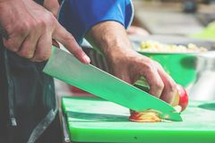 Chiuda su delle cipolle irriconoscibili di taglio del cuoco e di altre verdure con il coltello del cuoco unico mentre lavorano fotografia stock