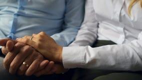 Chiuda su delle coppie adorabili che tengono insieme le mani