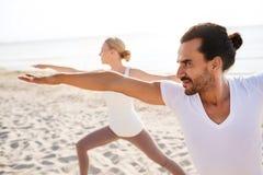 Chiuda su delle coppie che fanno gli esercizi di yoga all'aperto Immagini Stock