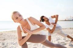Chiuda su delle coppie che fanno gli esercizi di yoga all'aperto Fotografie Stock