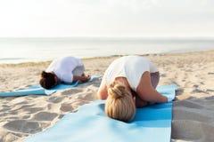 Chiuda su delle coppie che fanno gli esercizi di yoga all'aperto Immagine Stock Libera da Diritti