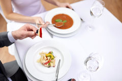 Chiuda su delle coppie che mangiano gli aperitivi al ristorante Immagine Stock