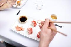 Chiuda su delle coppie che mangiano i sushi al ristorante Immagini Stock