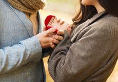 Chiuda su delle coppie con il contenitore di regalo in parco Fotografie Stock Libere da Diritti