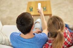 Chiuda su delle coppie con la TV di sorveglianza a distanza a casa fotografia stock