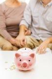 Chiuda su delle coppie con le monete ed il porcellino salvadanaio Fotografie Stock Libere da Diritti