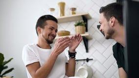 Chiuda su delle coppie gay stanno sedendo dietro il tavolo da cucina e stanno avendo prima colazione di mattina alla cucina Giova stock footage