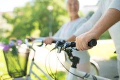 Chiuda su delle coppie senior con le biciclette di estate fotografia stock