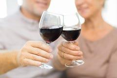 Chiuda su delle coppie senior felici con vino rosso Fotografia Stock