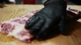 Chiuda su delle costole di manzo che sono preparate per la cottura nel ristorante costoso, movimento lento stock footage