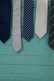 Chiuda su delle cravatte che appendono sulla parete di legno verde Immagini Stock