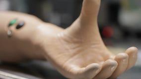 Chiuda su delle dita d'arricciatura della mano bionica sulla tavola video d archivio