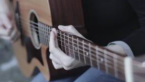 Chiuda su delle dita del chitarrista che giocano una chitarra acustica, con una profondità di campo bassa video d archivio