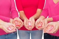Chiuda su delle donne con i nastri di consapevolezza del cancro Immagini Stock