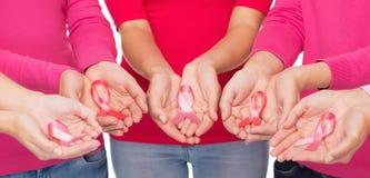 Chiuda su delle donne con i nastri di consapevolezza del cancro Fotografia Stock