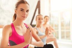 Chiuda su delle donne giovanili che fanno l'yoga Fotografia Stock
