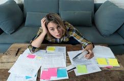 Chiuda su delle fatture di pagamento sollecitate ed enormi della giovane donna e delle finanze domestiche in carico fotografia stock