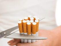 Chiuda su delle forbici che tagliano molte sigarette Immagine Stock Libera da Diritti