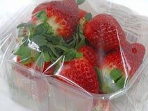 Chiuda su delle fragole fresche avvolte con stagnola in recipiente di plastica immagini stock
