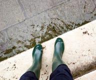 Chiuda su delle gambe con gli stivali dovuto l'alta marea a Venezia Immagini Stock