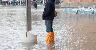 Chiuda su delle gambe con gli stivali dovuto l'alta marea a Venezia Fotografia Stock Libera da Diritti
