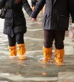 Chiuda su delle gambe con gli stivali dovuto l'alta marea a Venezia Immagine Stock Libera da Diritti