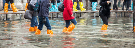 Chiuda su delle gambe con gli stivali dovuto l'alta marea a Venezia Immagine Stock