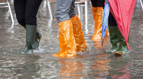 Chiuda su delle gambe con gli stivali dovuto l'alta marea a Venezia Immagini Stock Libere da Diritti