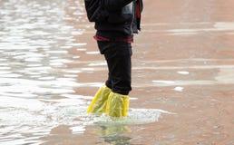 Chiuda su delle gambe con gli stivali dovuto l'alta marea a Venezia Fotografia Stock