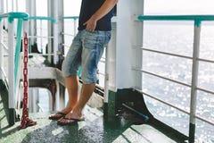 Chiuda su delle gambe del viaggiatore del giovane che sta sulla barca Fotografia Stock