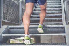 Chiuda su delle gambe dell'uomo con alto corrente delle scarpe da tennis le scale Sport, Fotografie Stock