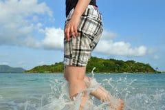 Chiuda su delle gambe della donna che camminano a piedi nudi nella spuma durante il summe Fotografie Stock