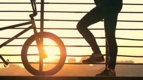 Chiuda su delle gambe della ruota e del maschio del ` s della bicicletta contro i precedenti della città video d archivio