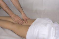 Chiuda su delle gambe di una donna che ricevono un massaggio dalle mani di un uomo Fotografia Stock Libera da Diritti