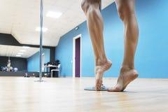 Chiuda su delle gambe forti nude di un poledancer che posa prima del poledance al fondo del corridoio di ballo Forte condizione d fotografie stock
