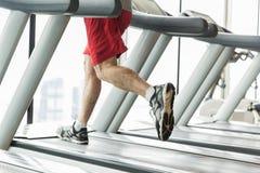 Chiuda su delle gambe maschii che corrono sulla pedana mobile in palestra Fotografia Stock