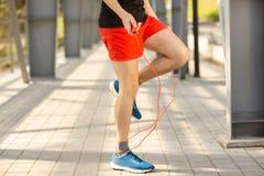 Chiuda su delle gambe maschii che saltano con la corda di salto all'aperto Concetto di stile di vita e di esercitazione fotografia stock