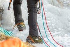 Chiuda su delle gambe rampicanti dell'alpinista del ghiaccio con gli stivali e le attrezzature dello sport professionale Fotografia Stock