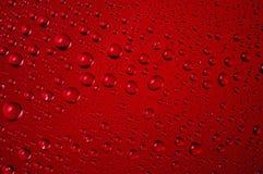 Chiuda su delle gocce di acqua su fondo rosso Fotografia Stock Libera da Diritti