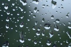 Chiuda su delle gocce di pioggia su una finestra immagini stock
