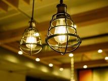 Chiuda su delle lampadine della luce gialla nelle gabbie del metallo fotografia stock libera da diritti