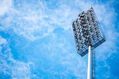 Chiuda su delle luci dello stadio con il fondo del cielo blu Immagini Stock